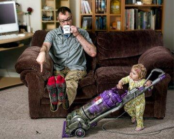 petite fille passant l'aspirateur devant son père