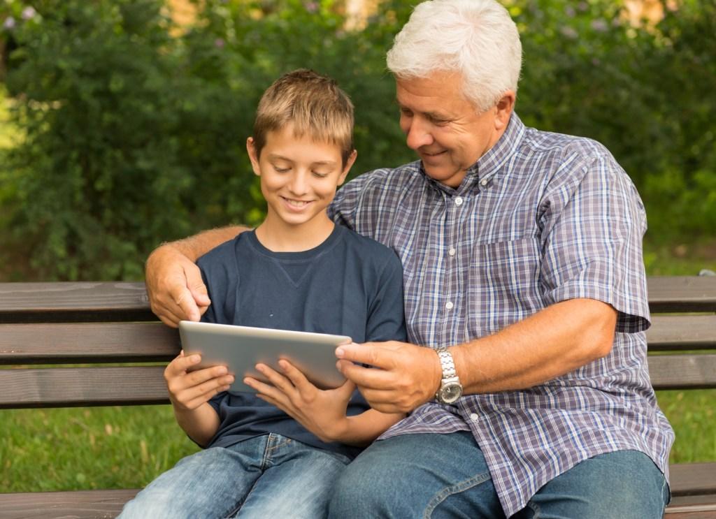 Sénior et enfant regardant une tablette