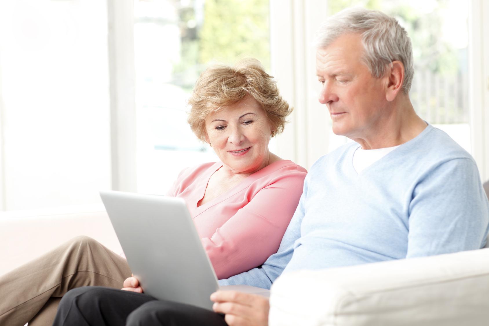 Couple de séniors lisant sur un ordinateur portable