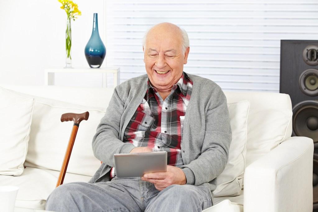 Senior assis sur canapé utilisant une tablette